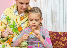 Mom shows how to lear. N to knit Stock Image