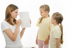 Mom shows the kids a white sheet of paper stock images