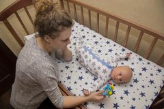 Mom shows rattle to his newborn child, who lies in a crib Stock Images