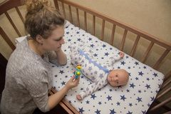 Mom shows rattle to his newborn child, who lies in a crib Stock Photography