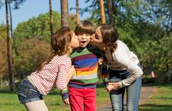 Mom and sister kiss the boy from both sides. Mom and sister kiss the boy from both sides in the park stock images