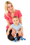 Mom sitting with a baby on the floor. Isolated on white background Stock Photography