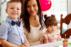 Mom sitting with children at birthday party Royalty Free Stock Photo