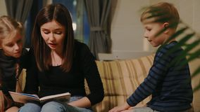 Mom sitting on the couch with his daughter and young son, reading them a story while sitting on the couch in their stock video
