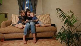 Mom sitting on the couch with his daughter and young son, reading them a story while sitting on the couch in their stock video footage