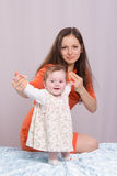 Mom with a six-month daughter on the bed. Mom and daughter on the couch six-month royalty free stock photography