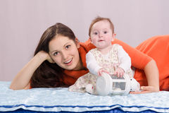 Mom with a six-month daughter playing on the bed. Mom and six-month daughter happily lie on the couch stock photo