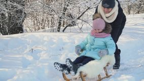 Mom rolls her daughter on a sled stock video footage