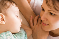 Mom with sleeping daughter Stock Images
