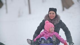 Mom slithering her little pretty daughter on a sled in a winter park. Winter family entertainment concept stock video