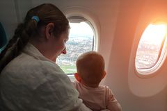 Mom with a small baby in her arms flying on the plane. They look out the window on the city with interest. Traveling with infant. Under one year stock image