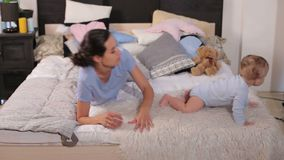 Mom with a small child lying on the bed on a fluffy blanket in the bedroom. Family having fun together. Mom and baby boy in diaper playing in bedroom stock footage