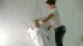 A mom and a small daughter removing old wallpaper. A young pregnant mom and a small daughter removing old white wallpaper stock video