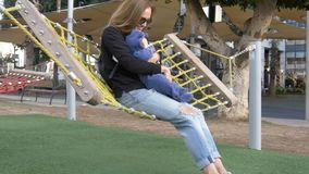 Mom and small funny baby have fun shakeing in hammock stock photo