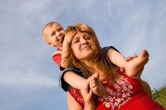 Mom and son. The son sits on shoulders at mîand smiles stock photography