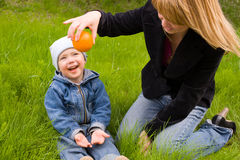 Mom and son. Mom and the son play with an orange on a lawn Stock Image