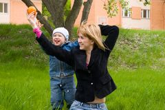 Mom and son. Mom and the son play with an orange on a grass. Spring Stock Photos