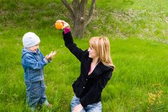 Mom and son. Mom and the son play with an orange on a grass. Spring Stock Images