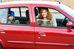 Mom and son. Young mother and her little son sitting in a red car and look at us Royalty Free Stock Photography
