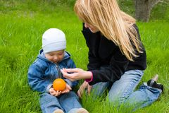 Mom and son. Mom and the son play with an orange on a grass. Spring Stock Photo