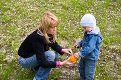 Mom and son. Mom and the son play with an orange on a grass. Spring Royalty Free Stock Photo