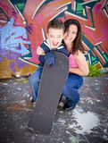 Mom and son. Pretty mom and son with skateboard playing Stock Images
