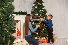 Mom with son adorn the Christmas tree lights Christmas new year. Gifts stock images