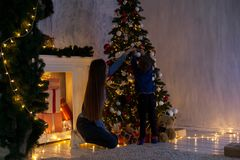 Mom with son adorn the Christmas tree lights Christmas new year. Gifts stock photo