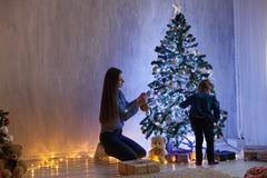 Mom with son adorn the Christmas tree lights Christmas new year. Gifts royalty free stock photo