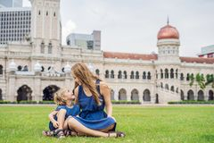 Mom and son on background of Merdeka square and Sultan Abdul Samad Building. Traveling with children concept.  royalty free stock image
