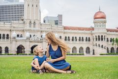 Mom and son on background of Merdeka square and Sultan Abdul Samad Building. Traveling with children concept.  stock photos