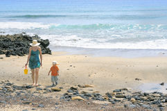 Mom and son on the beach. Mother and her two year old boy carrying water from the sea in a toy bucket; Graciosa, Canary islands, Spain stock photo