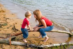 Mom.son.beach. Mom and the son talk at the sea.Evening Stock Photos