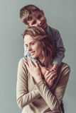 Mom and son. Beautiful women and her cute little son are hugging and smiling, on gray background. Boy is looking at camera Royalty Free Stock Photo