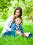 Mom and son with book in park Royalty Free Stock Photo