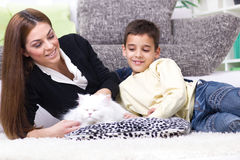 Mom and son caress white Persian cat. Mom and son lying on the floor and caress white Persian cat Royalty Free Stock Images