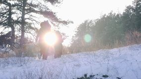 Mom and son climb snow-covered hill in backlight in slow motion at winter forest. Mom and son climb the snow-covered hill in backlight in slow motion at winter stock video