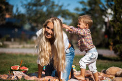 Mom son climbs on her shoulders. Mother with kids have fun on the grass stock photo