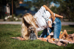 Mom son climbs on her shoulders. Mother with kids have fun on the grass stock images