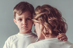 Mom and son. Cute little boy is hugging his mom and looking sadly at camera, on gray background Royalty Free Stock Images