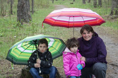 Mom with son and daughter sitting in the woods under umbrellas. Stock Photo
