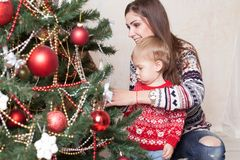 Mom with son decorate tree on new year`s Gifts Christmas Royalty Free Stock Photo