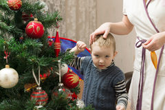 Mom and son decorate the Christmas tree Royalty Free Stock Image