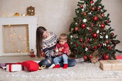 Mom with son decorate tree on new year`s Gifts Christmas Royalty Free Stock Photos