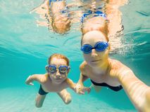 Mom and son in diving glasses swim in the pool under the water.  stock photos