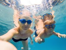 Mom and son in diving glasses swim in the pool under the water.  royalty free stock photos