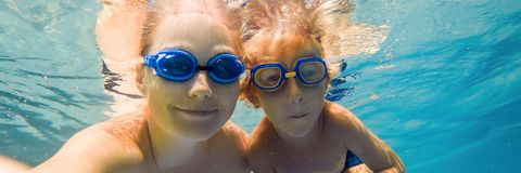 Mom and son in diving glasses swim in the pool under the water BANNER, long format. Mom and son in diving glasses swim in the pool under the water. BANNER, long royalty free stock photo