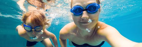 Mom and son in diving glasses swim in the pool under the water BANNER, long format. Mom and son in diving glasses swim in the pool under the water. BANNER, long stock photos