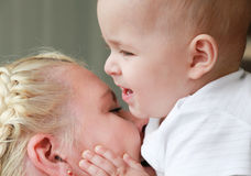 Mom and son doing funny and rough kissing. Baby touch cheek of mother Stock Image