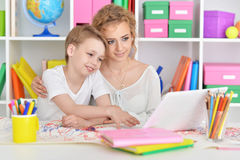Mom and son doing lessons. At the table Royalty Free Stock Photos